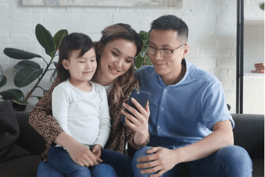 A family smiling looking at one smartphone screen in the room